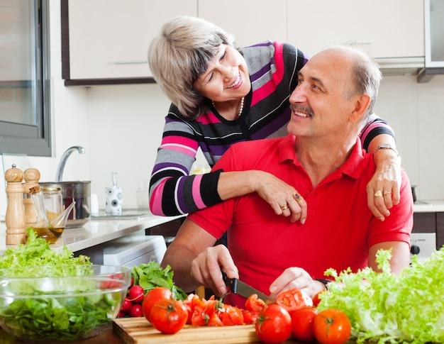 Homme senior et femme cuisine déjeuner ensemble