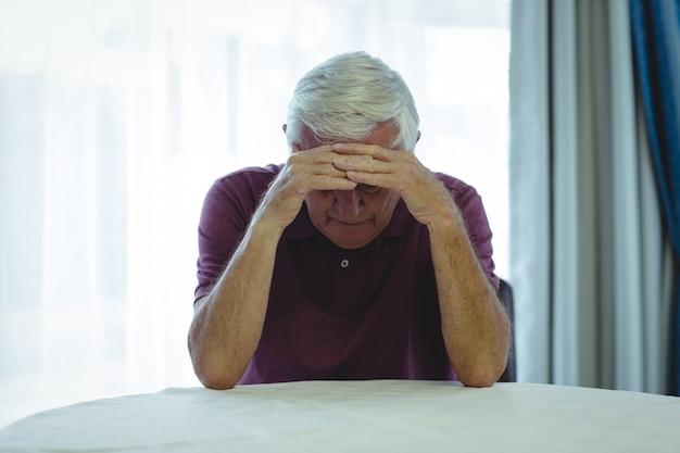 Homme senior inquiet assis dans le salon