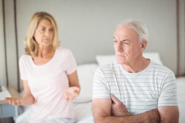 Homme senior inquiet assis sur le lit