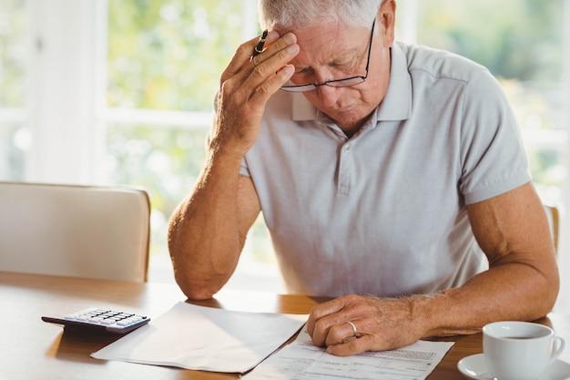 Homme senior inquiet avec des documents fiscaux à la maison