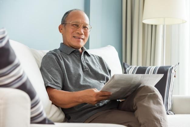 Homme senior lisant un journal
