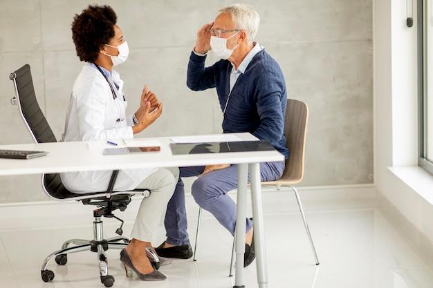 Un homme senior avec un masque facial de protection reçoit des nouvelles d'une femme médecin noire au bureau