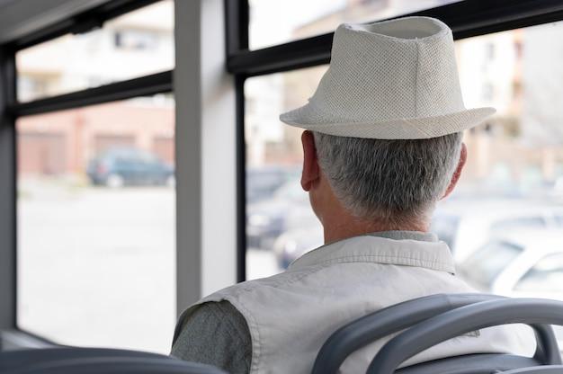 Homme senior moderne assis dans le bus