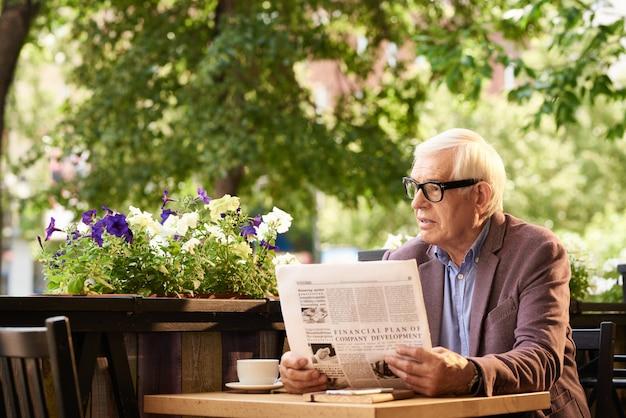 Homme senior moderne lisant le journal dans le café en plein air