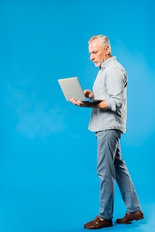 Homme senior moderne avec ordinateur portable