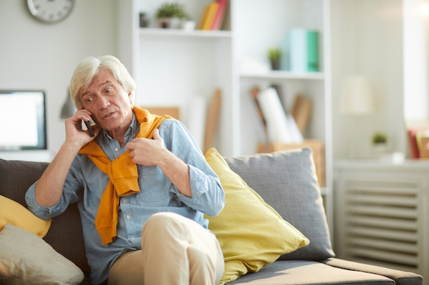 Homme senior moderne parlant par téléphone dans le salon