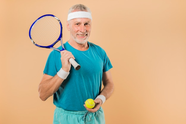 Homme senior moderne avec une raquette de tennis