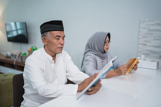 Homme senior musulman asiatique enseignant à sa femme la lecture du coran ou du coran dans le salon. couple musulman priant à la maison