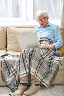 Homme senior occupé avec une couverture sur les jambes assis sur un canapé et utilisant internet sur ordinateur portable