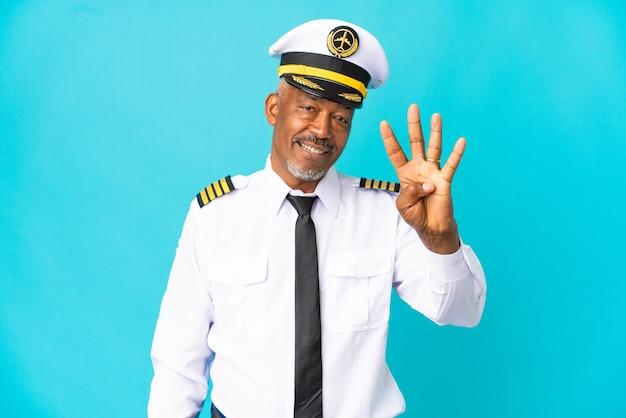 Homme senior pilote d'avion isolé sur fond bleu heureux et comptant quatre avec les doigts