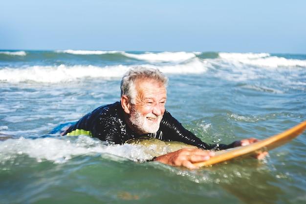 Un homme senior sur une planche de surf