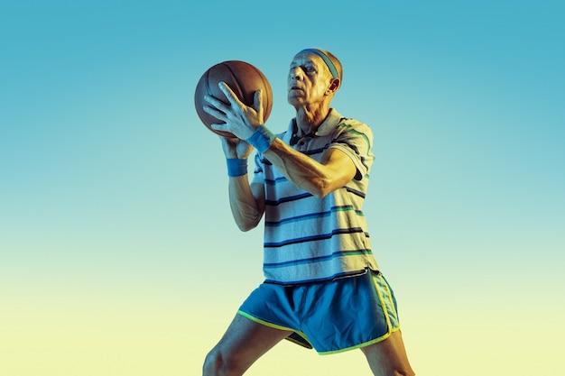 Homme senior portant des vêtements de sport jouant au basket-ball sur fond dégradé, néon. le modèle masculin caucasien en pleine forme reste actif. concept de sport, activité, mouvement, bien-être, confiance.