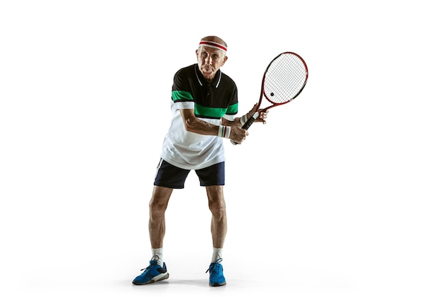 Homme senior portant des vêtements de sport jouant au tennis isolé sur fond blanc. le modèle masculin caucasien en pleine forme reste actif et sportif. concept de sport, activité, mouvement, bien-être. copyspace, annonce.