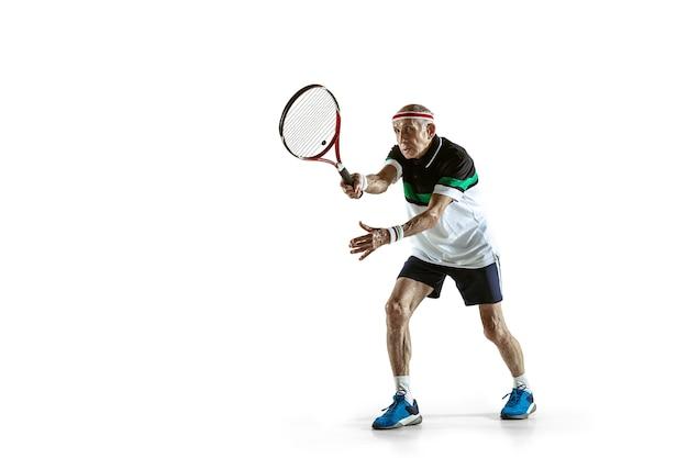 Homme senior portant des vêtements de sport jouant au tennis isolé sur un mur blanc. le modèle masculin caucasien en pleine forme reste actif et sportif. concept de sport, activité, mouvement, bien-être. copyspace, annonce.