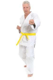 Homme senior en pose de karaté sur fond blanc
