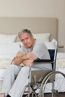 Homme senior réfléchi dans son fauteuil roulant
