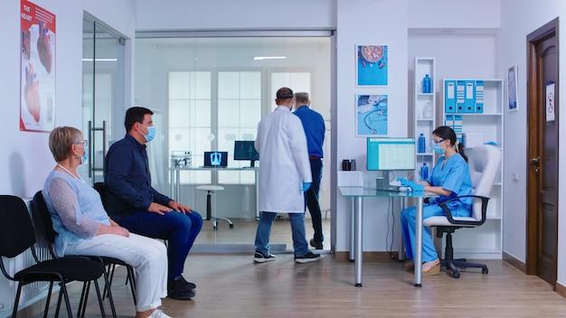 Homme senior remplissant le document dans la salle d'attente de l'hôpital avant l'examen médical. infirmière portant un masque facial contre l'infection par le coronavirus. zone d'attente occupée de l'hôpital privé