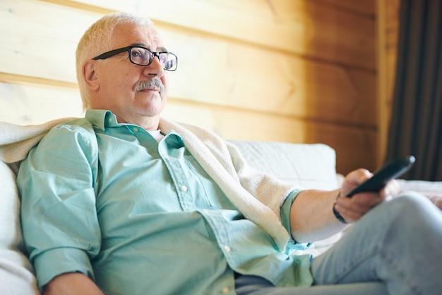 Homme senior reposant à lunettes et vêtements décontractés à l'aide de la télécommande tout en regardant la télévision dans sa maison de campagne
