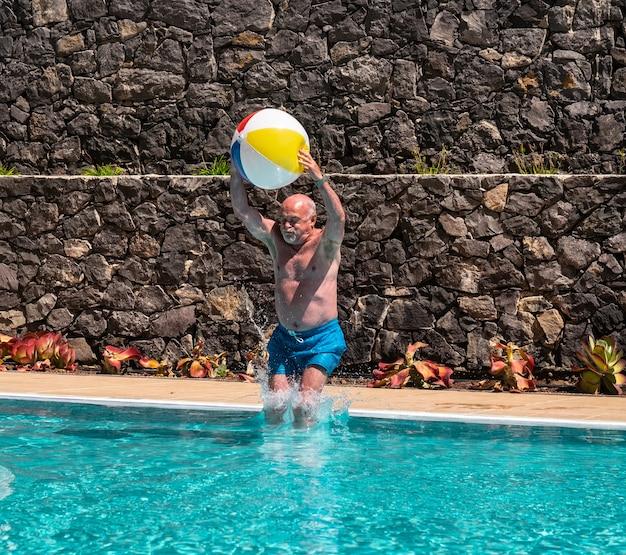Un homme senior saute dans la piscine avec un gros ballon dans les mains. l'été et le plaisir. jouer avec des amis. barbe et poils blancs