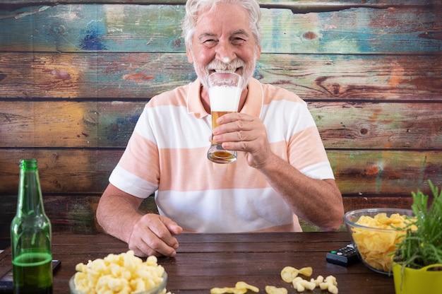 Homme senior séduisant assis à une table en bois tenant un verre de bière blonde, regardant la caméra en souriant