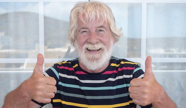 Homme senior séduisant barbe blanche et cheveux faisant des gestes ok avec les mains en plein air sur la terrasse. expression drôle. t-shirt rayé coloré