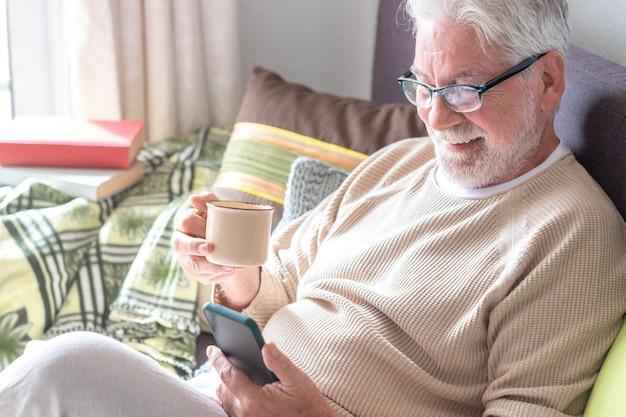 Homme senior séduisant, cheveux blancs, assis sur un canapé à la maison, buvant un café en regardant un téléphone portable