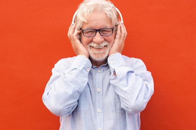 Homme senior séduisant debout sur fond rouge portant des écouteurs écoutant de la musique. les gens de race blanche sourient sans soucis
