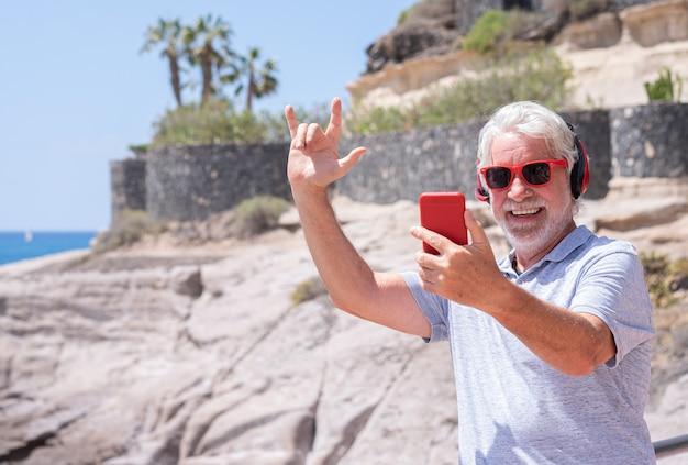 Homme senior séduisant et joyeux utilisant un téléphone portable à la mer, portant des écouteurs rouges. retraite drôle et heureuse. horizon au-dessus de l'eau