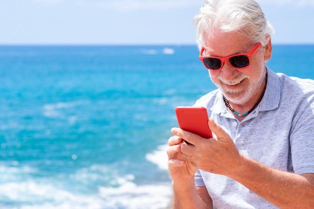 Homme senior séduisant en vacances à la mer, utilisant le téléphone et souriant. mer bleue et horizon au-dessus de l'eau