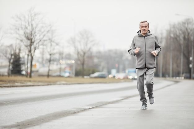 Homme senior sérieux en costume de sport gris balançant les bras en courant le long de la route en ville