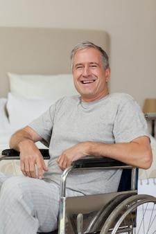 Homme senior souriant dans son fauteuil roulant à la maison