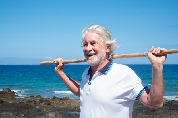 Homme senior souriant faisant des exercices de dos à l'aide d'une canne. ciel bleu et mer derrière lui. mode de vie sain. vacances ou retraite. sérénité et détente