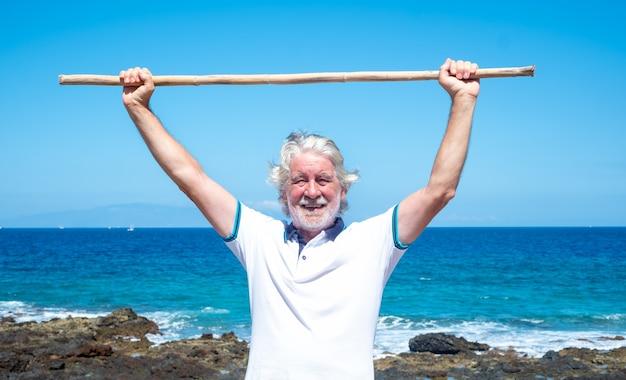 Homme senior souriant faisant des exercices d'épaule à l'aide d'une canne. ciel bleu et mer derrière lui. mode de vie sain. vacances ou retraite. sérénité et détente