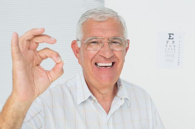 Homme senior souriant gesticulant ok avec le tableau de l'oeil en arrière-plan
