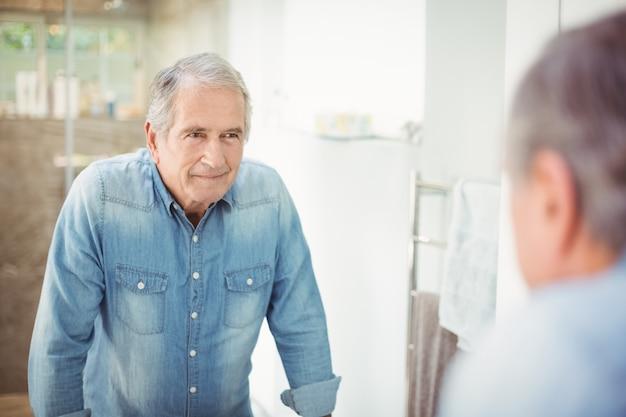Homme senior souriant sur miroir
