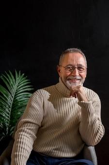 Homme senior souriant se frottant le menton