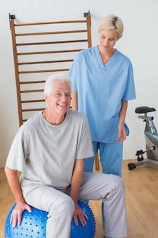 Homme senior souriant avec son thérapeute dans un studio de fitness