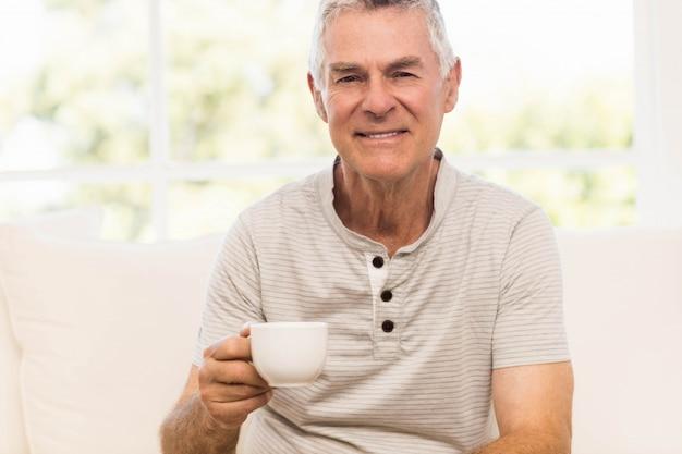 Homme senior souriant, tenant la tasse assis sur le canapé