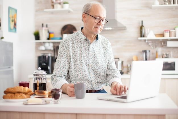 Homme senior souriant et utilisant un ordinateur portable dans la cuisine. vie quotidienne d'un homme âgé dans la cuisine pendant le petit-déjeuner à l'aide d'un ordinateur portable tenant une tasse de café. personne âgée à la retraite travaillant à domicile, télétravaillant u