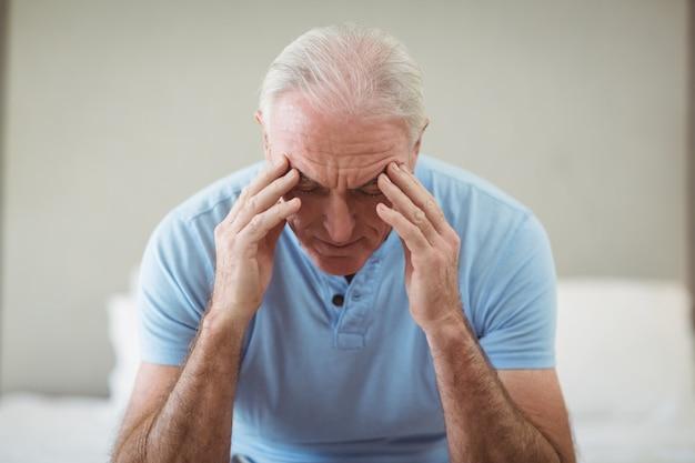 Homme senior stressé assis sur le lit