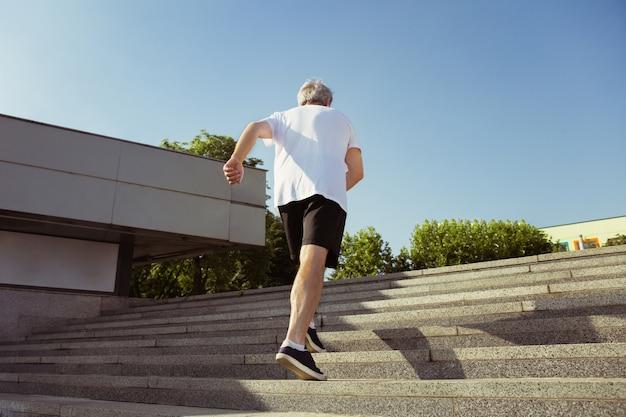 Homme senior en tant que coureur avec brassard ou tracker de fitness dans la rue de la ville. modèle masculin caucasien pratiquant le jogging et les entraînements cardio le matin d'été. mode de vie sain, sport, concept d'activité.