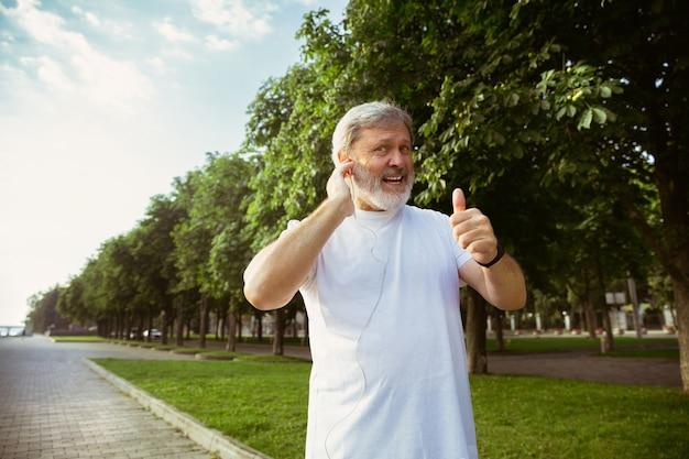 Homme senior en tant que coureur avec tracker de remise en forme dans la rue de la ville. modèle masculin de race blanche à l'aide de gadgets pendant le jogging et l'entraînement cardio le matin d'été. mode de vie sain, sport, concept d'activité.