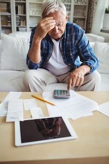 Homme senior tendu vérifiant les factures