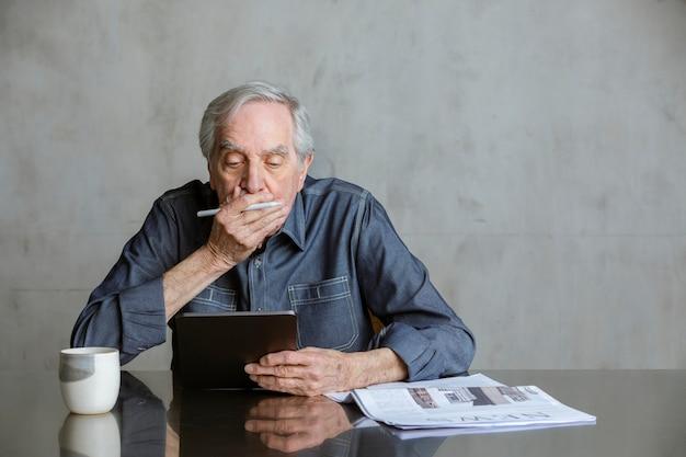 Homme senior vérifiant la mise à jour des actualités covid-19 sur une tablette avec une tasse et un journal sur la table