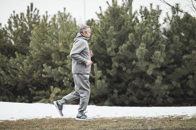 Homme senior en vêtements confortables gris courant sur la neige tout en s'entraînant seul dans la forêt