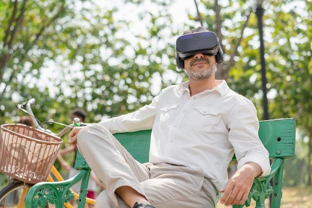 Homme senoir se relaxant à l'aide de lunettes de réalité virtuelle ou d'un casque vr assis sur un banc dans un parc