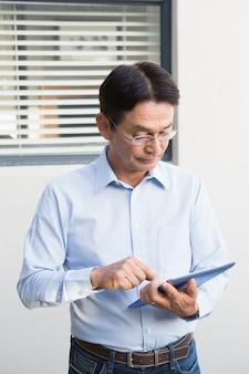 Homme sérieux à l'aide d'une tablette dans son jardin