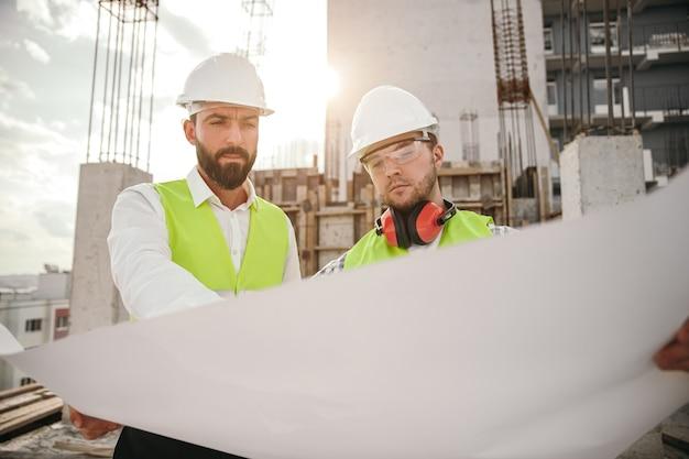 Homme sérieux architecte et ingénieur en casques d'analyse et de discussion de plan tout en travaillant ensemble sur un chantier de construction avec un bâtiment en béton