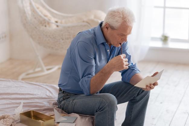 Homme sérieux et attentionné assis sur le lit et mordant ses lunettes tout en étant impliqué dans la lecture d'une vieille carte postale