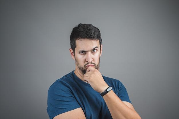 Homme sérieux au regard intense, regardant et levant un sourcil